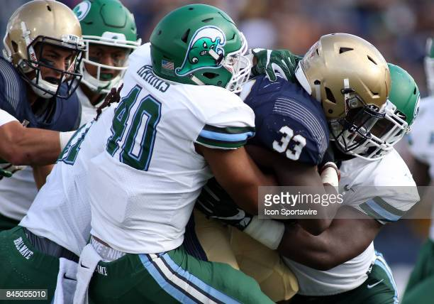 Navy Midshipmen fullback Chris High gets stuffed behind the line of scrimmage by multiple Tulane Green Wave defenders during a match between Tulane...