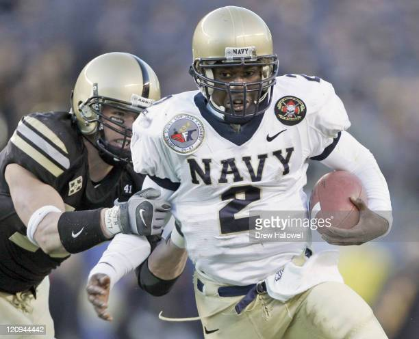 Navy Midshipmen quarterback Lamar Owens gets held up by Army Cadet defensive back Caleb Campbell while making a touchdown run during the second...