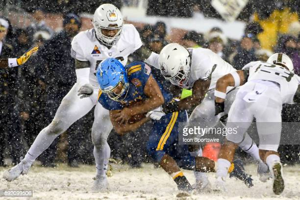 Navy Midshipmen quarterback Malcolm Perry is brought down by Army Black Knights defensive back Gibby Gibson and defensive back Elijah Riley on...