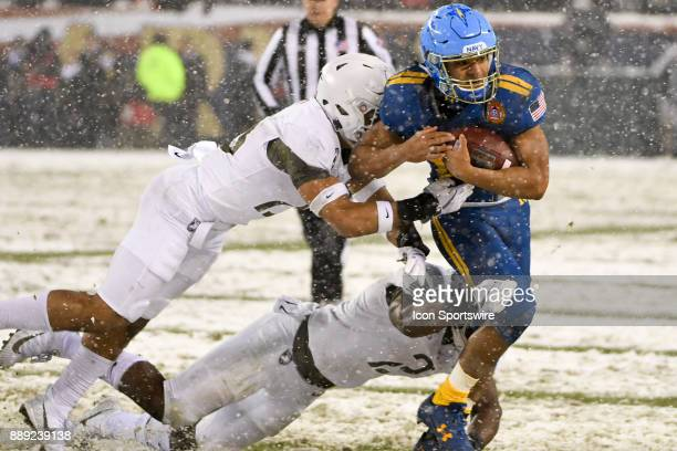 Navy Midshipmen running back Malcolm Perry runs for a first down in the fourth quarter and is brought down by Army Black Knights defensive back...