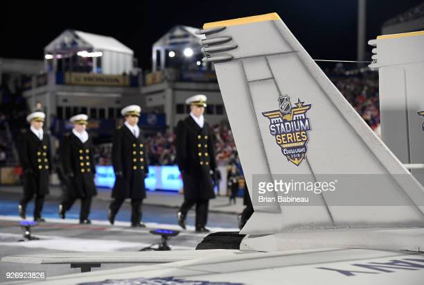 Navy midshipmen walk off the field past a Stadium Series logo prior to the the 2018 Coors Light NHL Stadium Series game between the Toronto Maple...