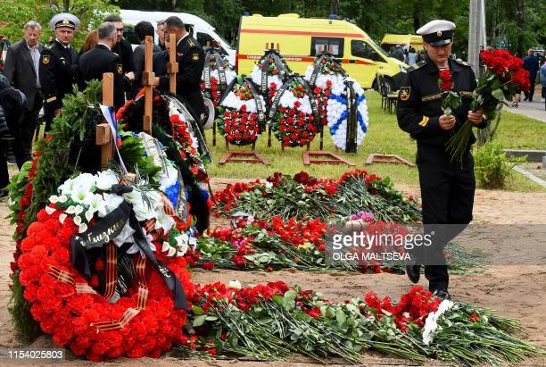 A navy officer mourns after a funeral ceremony at a cemetery in Saint Petersburg on July 6 three days after a fire that killed 14 officers on what...