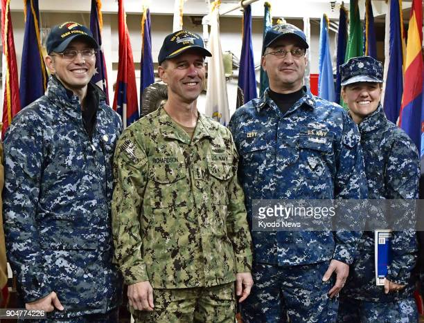 A US Navy officer poses for photos while wearing a new camouflage uniform while others wear the current gear aboard US aircraft carrier Ronald Reagan...