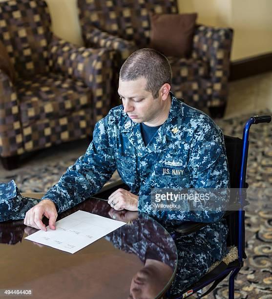 marinha americana auditor sentado na cadeira de rodas a leitura do documento - objetivo militar imagens e fotografias de stock