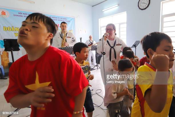 S Navy officers during a visit to a hospice supporting Agent Orange victims on March 7 2018 in Danang Vietnam The United States aircraft carrier USS...