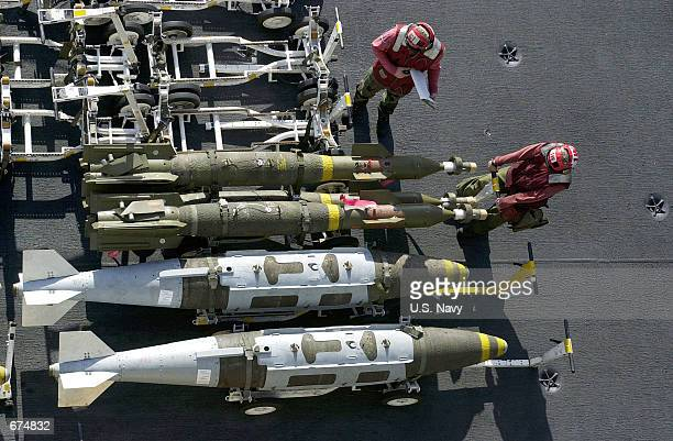 Navy Ordnancemen prepare to move three guided bomb units laser guided bombs parked next to two Joint Direct Attack Munition bombs November 28, 2001...