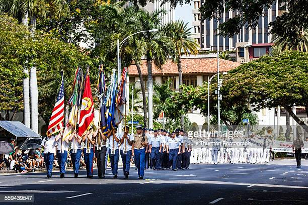 US Navy Pacific Band wearing white military uniforms following a color guard marching and playing brass instruments in the annual downtown King...