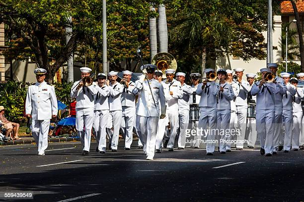 US Navy Pacific Fleet Band wearing white military uniforms marching and playing brass instruments in the annual downtown King Kamehameha Day Parade...