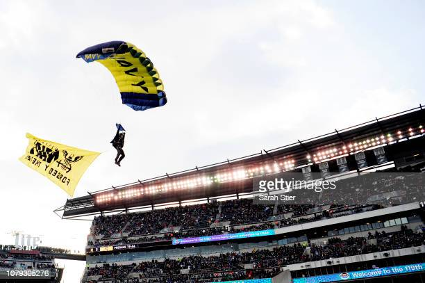 S Navy parachute jumper glides toward the field before the start of the game between Army Black Knights and Navy Midshipmen at Lincoln Financial...