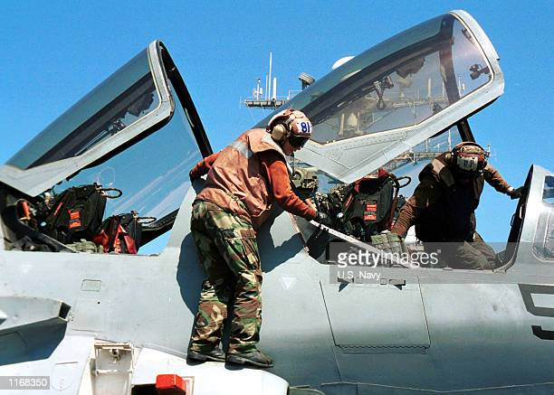 """Navy personnel conduct daily checks on their EA-6B """"Prowler"""" October 22, 2001 while onboard the USS aircraft carrier Carl Vinson. The USS Carl Vinson..."""