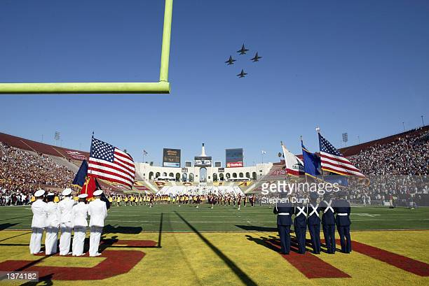 Navy pilots Marc Preston Brian Reeves Scott Bonz and Dave Kindley fly in formation over the field in F18 fighter jets during the National Anthem...