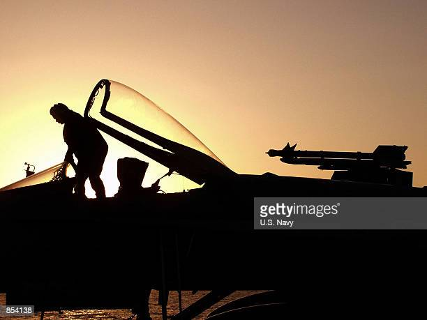 """Navy plane captain performs an early morning pre-flight check on a F/A-18 """"Hornet"""" strike fighter October 27, 2001 on the flight deck of the aircraft..."""