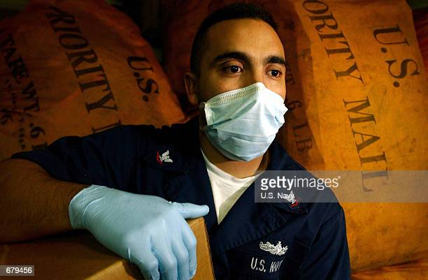 Navy Postal Clerk 3rd Class Eric Gomez wears a protective mask and gloves as he handles mail November 3, 2001 on board the Aaircraft carrier USS Carl...