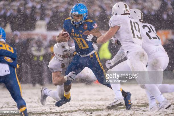 Navy QB Malcolm Perry is dragged down by Army LB Cole Christiansen in the second half during the game between The Army Black Knights and Navy...