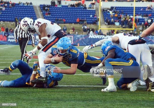 Navy quarterback Zach Abey scores from the 1yard line in the fourth quarter against Virginia in the Military Bowl at NavyMarine Corps Memorial...