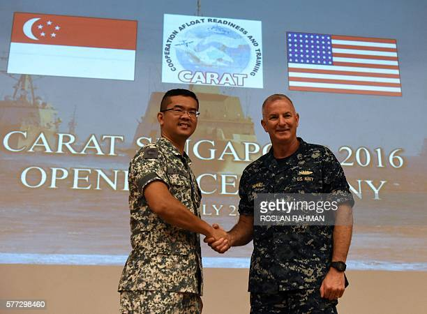 US Navy Rear Admiral Brian Hurley commander of Logistics Group Western Pacific/Task Force 73 shakes hands with Republic of Singapore Navy Fleet...