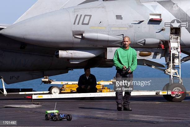 S Navy sailor Egary Tyler from Tucson Arizona races a radio controlled car on the deck of the USS Constellation December 26 2002 in the Persian Gulf...