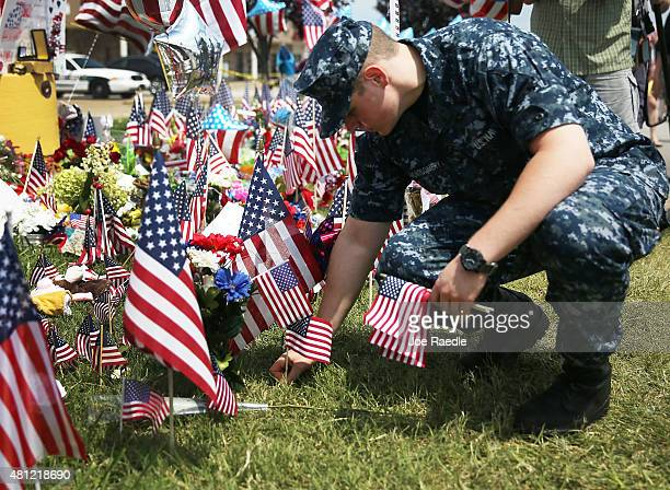 S Navy sailor Evan Montgomery places American flags in a memorial setup in front of the Armed Forces Career Center/National Guard Recruitment Office...