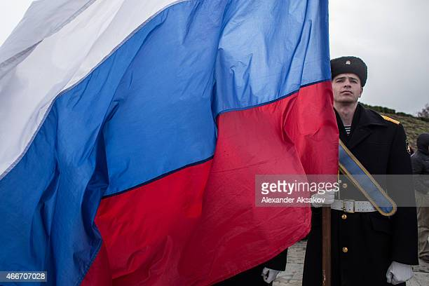 Navy sailor holds a Russian flag as people celebrate the first anniversary of the signing of the decree on the annexation of the Crimea by the...