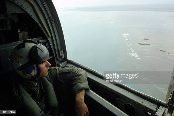 Navy sailor looks out at the Djibouti coastline from a U.S. Navy C-46 helicopter on its way from Camp Lemonier to the USS Mount Whitney February 26,...