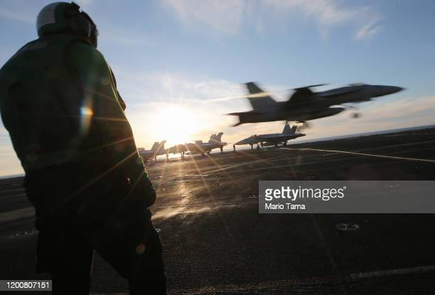 S Navy sailor maintenance worker keeps watch on the flight deck during flight operations aboard the USS Nimitz aircraft carrier while at sea on...
