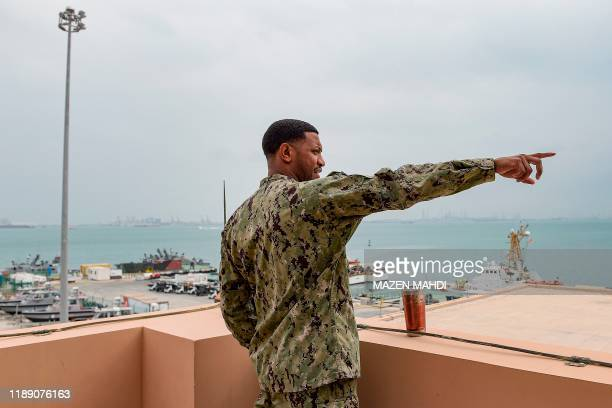 Navy sailor points with his finger as he stands aboard the observation deck overlooking docked US and coalition ships at the US 5th Fleet Command in...