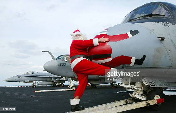 S Navy sailor Rick Pellicciotti from Follansbee West Virginia dressed as Santa Claus clowns around with the painted nose cone of a S3B Viking on the...