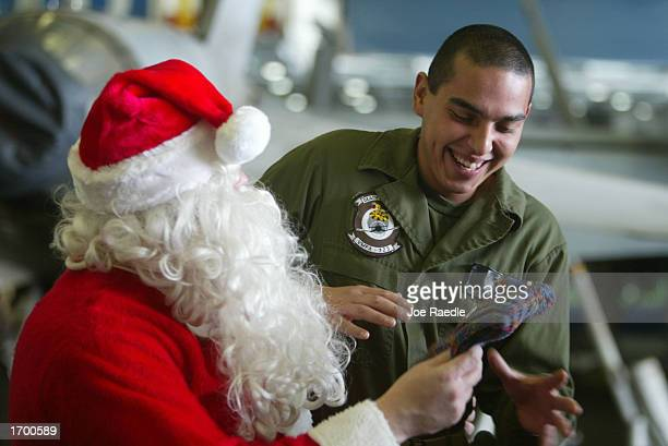 S Navy sailor Rick Pellicciotti from Follansbee West Virginia dressed as Santa Claus gives a gift to Lance Corp Arnoldo Sanches from San Jose...