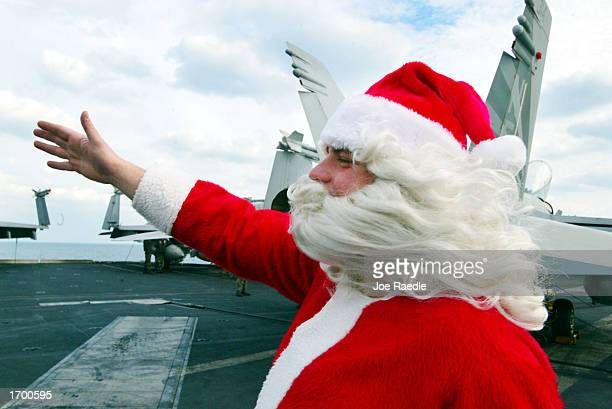 S Navy sailor Rick Pellicciotti from Follansbee West Virginia dressed as Santa Claus waves to sailors on the deck of the USS Constellation December...