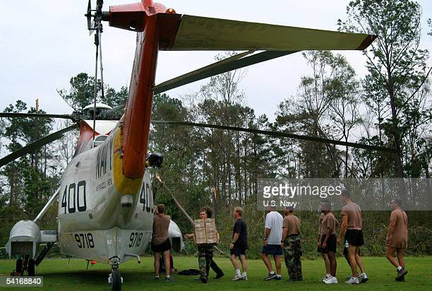 S Navy Sailors and civilian personnel unload food and water from a UH3H Sea King helicopter transported from Naval Air Station Pensacola Florida to...