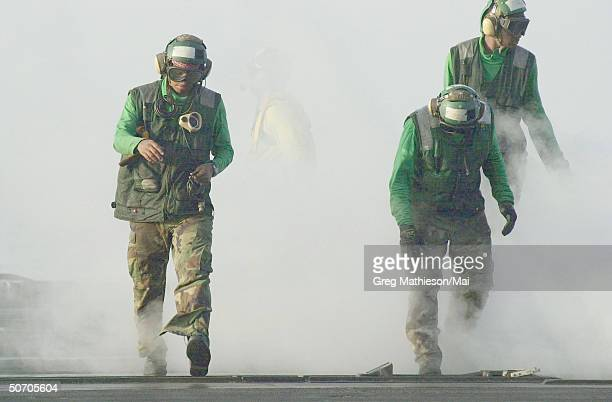 US Navy Sailors assigned to the catapult crew aboard the aircraft carrier USS Carl Vinson preparing the launch area for the next launch from the...