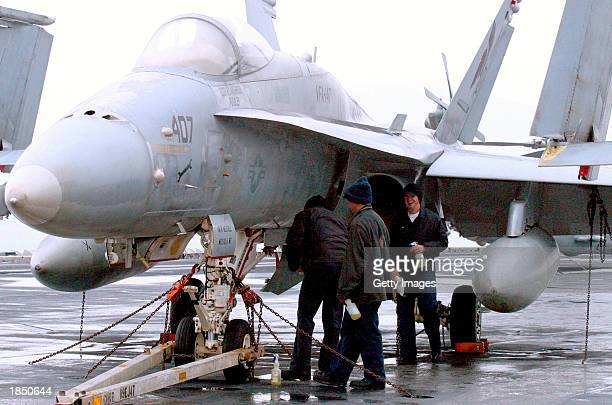 Navy sailors check a U.S. Fighter jet on the deck of aircraft carrier USS Carl Vinson after arriving at Pusan Port to participate in the joint...