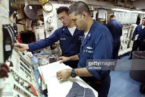 Navy sailors Cliff Cavales from Dumaguete City, Philippines and Jagdeep Sidhu from Las Vegas, Nevada work on the propulsion panel in the USS Fletcher...