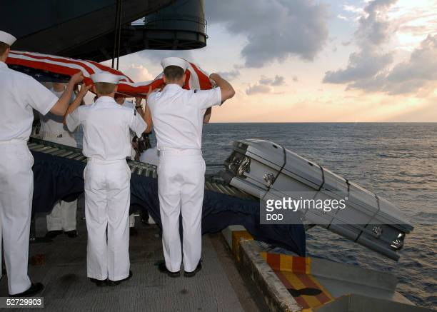 S Navy sailors perform a burial at sea ceremony for US Navy Machinist's Mate Third Class Nathan Taylor on the the USS Enterprise May 19 in this photo...