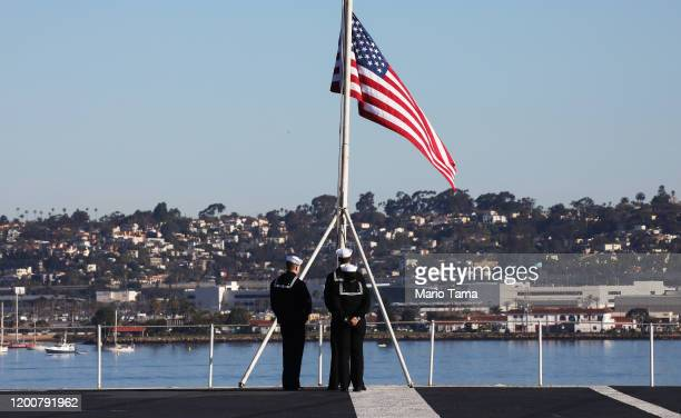S Navy sailors prepare to take down the flag on the flight deck of the USS Nimitz aircraft carrier on January 18 2020 in Coronado California The USS...