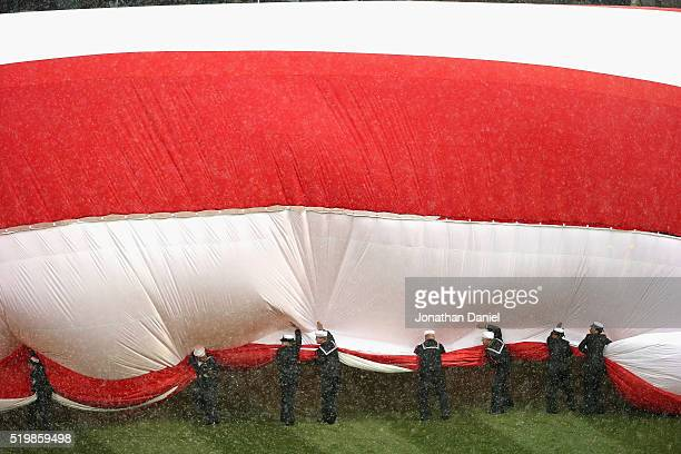 S Navy sailors try to corral a large American flag during a snow squall before the home opener between the Chicago White Sox and the Cleveland...