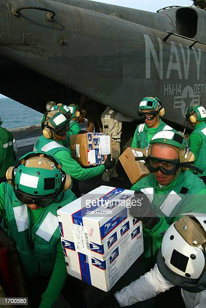 S Navy sailors unload boxes of mail and gifts from the back of a helicopter on the deck of the USS Constellation December 24 2002 in the Persian Gulf...