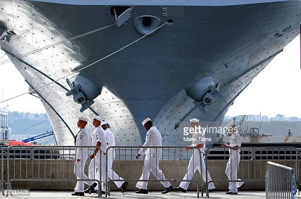 S Navy sailors walk past the USS Iwo Jima docked on the Hudson River during Fleet Week May 22 2009 in New York City Fleet Week which annually brings...