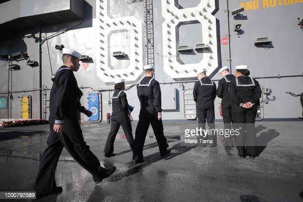 Navy sailors walk with the flag on the flight deck of the USS Nimitz aircraft carrier on January 18, 2020 in Coronado, California. The USS Nimitz is...