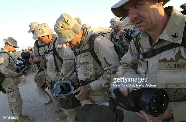 Navy Seabees inspect their gas masks at Al Jaber Air Base in the Kuwaiti desert American troops and equipment are massed in Kuwait in readiness for a...
