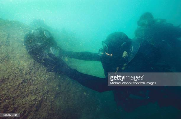 u.s. navy seal combat swimmers place a mk-1 limpet mine onto a target. - limpet stock photos and pictures