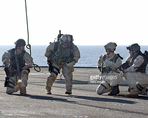 S Navy SEAL completes rappeling from a helicopter to the deck of the amphibious command ship USS Mount Whitney during a training exercise January 17...