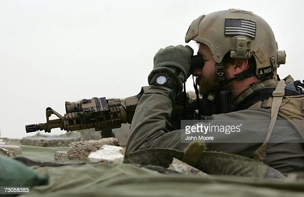 Navy Seal looks towards insurgent movements from the rooftop of an observation post January 21, 2007 in Ramadi in the Anbar province of Iraq. With...