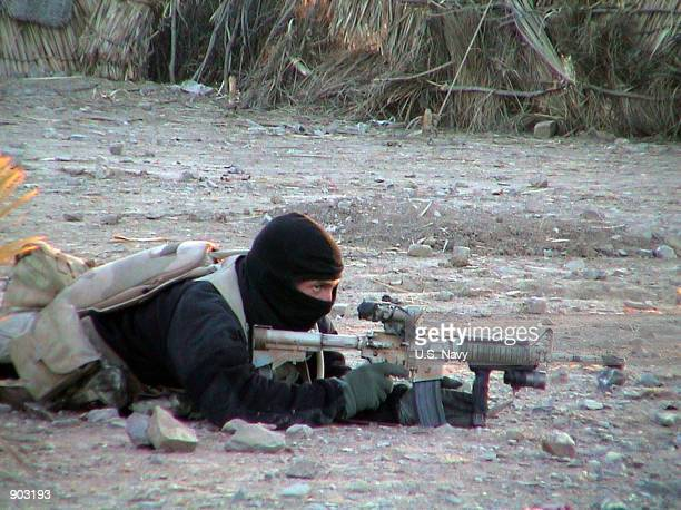 Navy SEAL member provides cover for his teammates advancing on a suspected location of al Qaeda and Taliban forces January 26, 2002 in Eastern...
