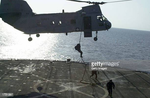 S Navy SEAL rappels from an CH46D Sea Knight helicopter to the deck of the amphibious command ship USS Mount Whitney during a training exercise...