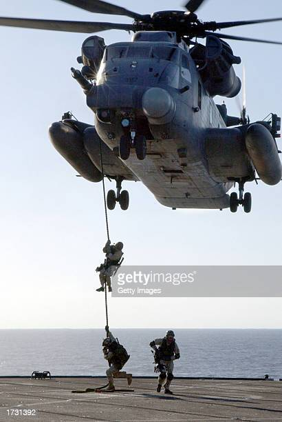 S Navy SEAL rappels from an MH53 'Pave Low' helicopter to the deck of the amphibious command ship USS Mount Whitney during a training exercise...