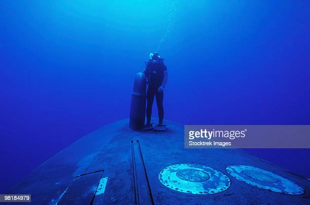 A Navy SEAL stands next to the sonar dome on the bow of the USS Kamehameha.