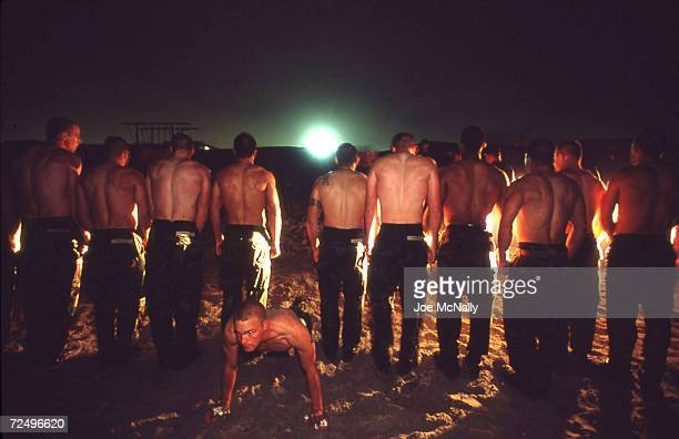 Navy Seal trainee executes pushups in the sand as other trainees stand in line in this undated photo taken in 2000 at the Coronado Naval Amphibious...
