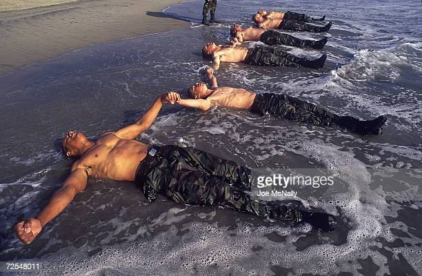 Navy Seal trainees lie in the frigid Pacific surf in this undated photo taken in 2000 at the Coronado Naval Amphibious Base in San Diego, California....