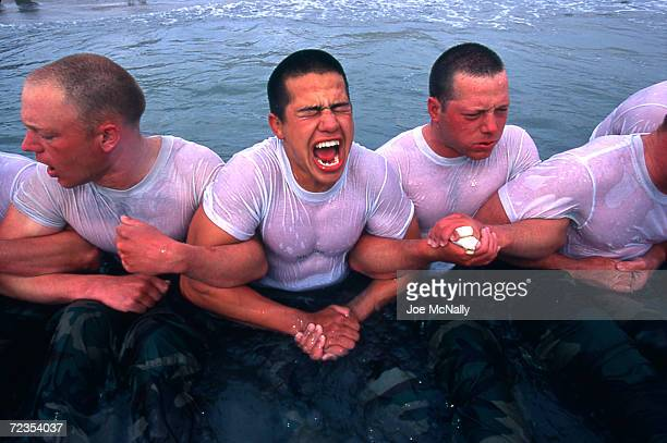 Navy Seal trainees lock arms upon entering the frigid Pacific waters in this undated photo taken in 2000 at the Coronado Naval Amphibious Base in San...